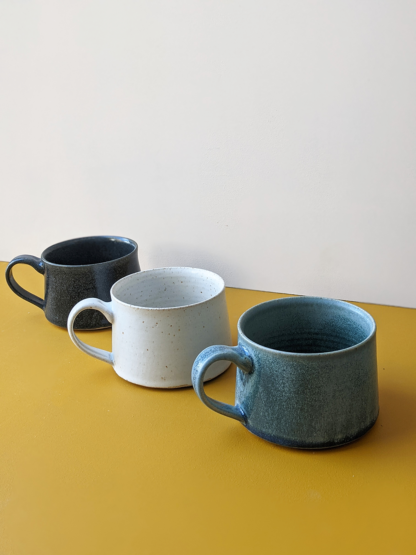 three handmade ceramic crafted mugs in different glaze colours