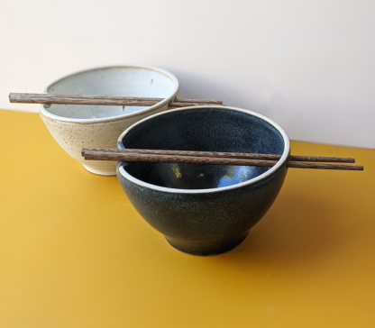 Two handmade ceramic crafted ramen noodle bowls in black and cream glaze colours with wooden chopsticks