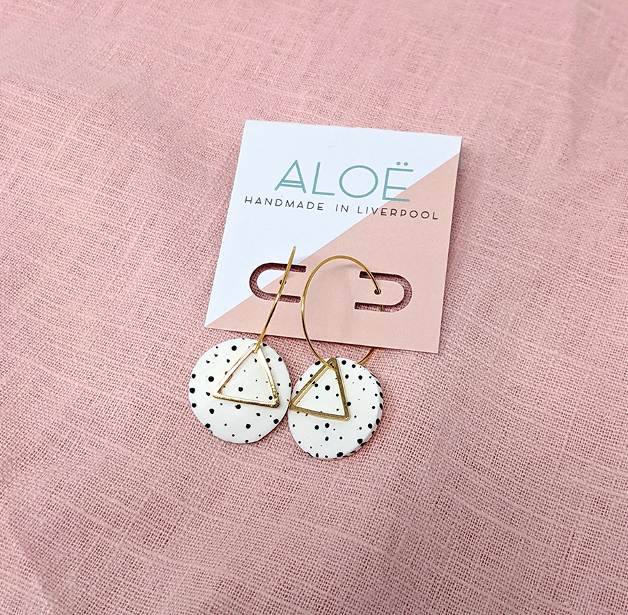 gold hooped earrings with a black and white spotted disc and golden triangle pendant