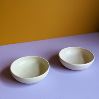 two handmade crafted organic cream ceramic dishes placed adjacently