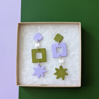 Handmade fimo clay lilac and green shape earrings sat in a gift box