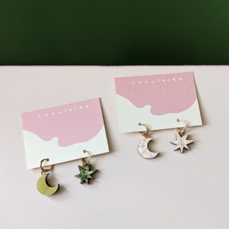 two pairs of dainty gold hoop earrings with star and moon pendants