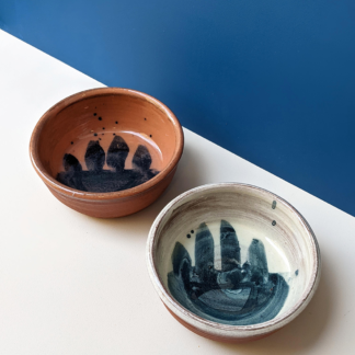two shallow terracotta ceramic dishes with white or cobalt blue glaze